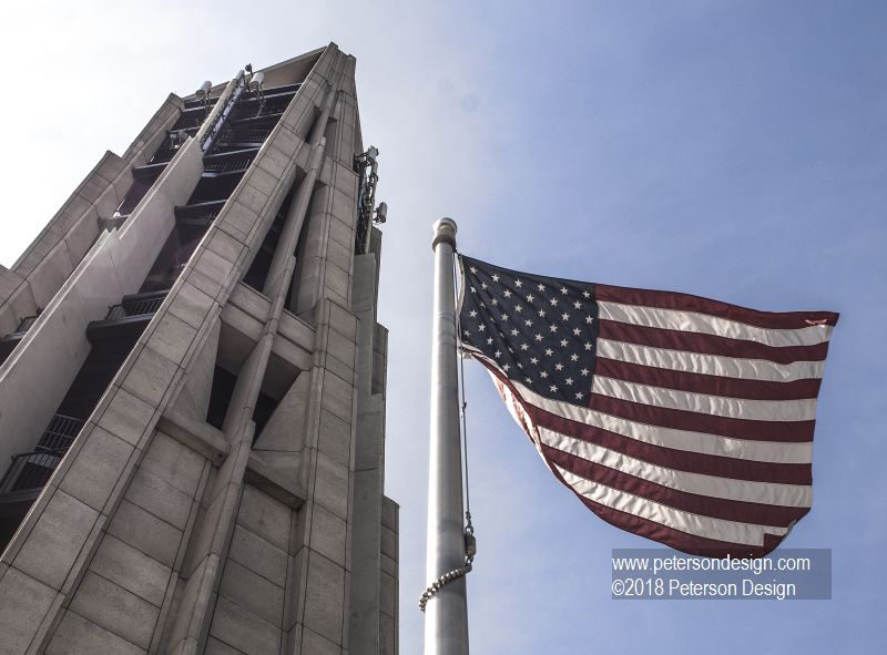 Image of Naperville's Carrilon Bell Tower alongside a waving american flag